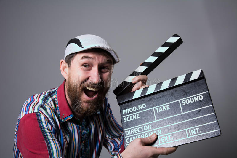 Smiling man with clapper movie. Bearded man movie production of the comedy The assistant royalty free stock images