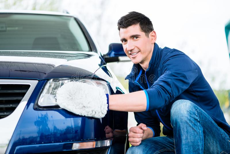 Smiling man cleaning the headlamp on his car. Wiping it with a mitt as he crouches alongside the vehicle stock photo