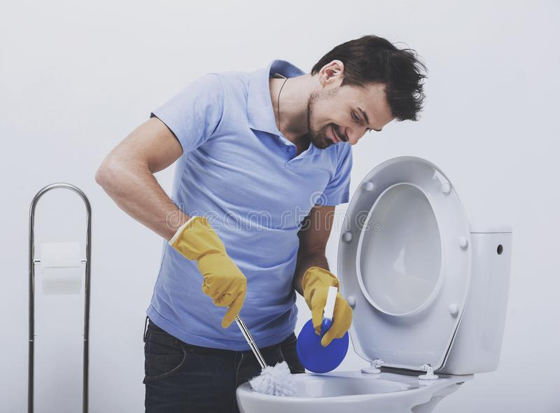 Smiling man is cleaning toilet with brush. stock photo