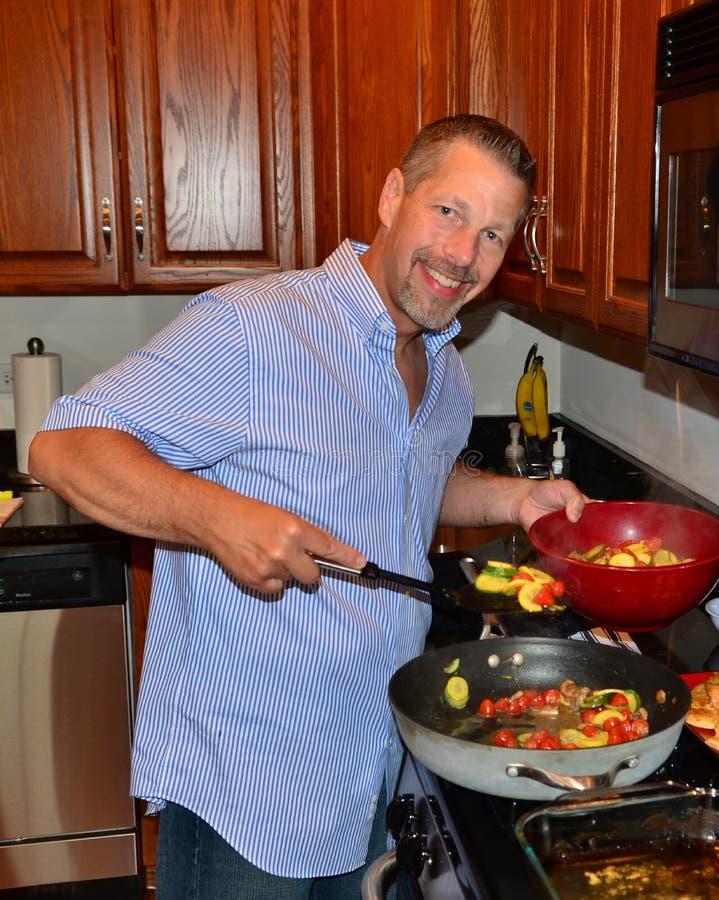 Smiling man cooking. Spooning vegetables pan bowl royalty free stock photo