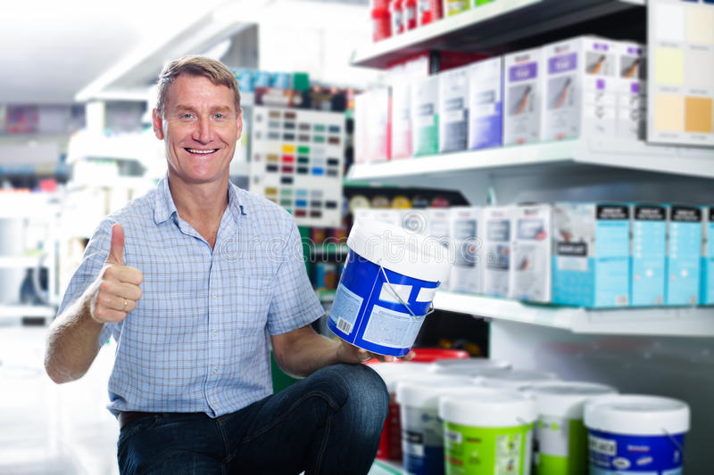 Smiling man customer choosing paint bucket in hypermarket stock images