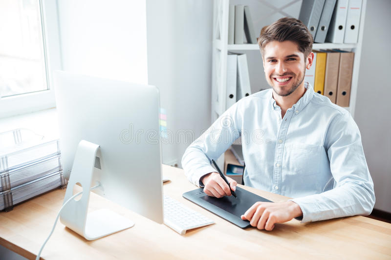 Smiling man designer working and using graphic tablet in office stock photography