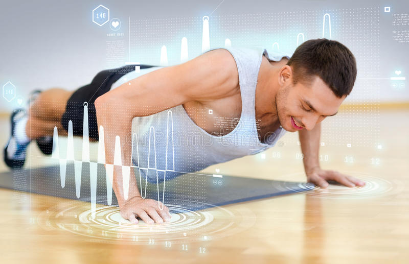 Smiling man doing push-ups in the gym. Fitness, sport, training, gym and lifestyle concept - smiling man doing push-ups in the gym stock photography