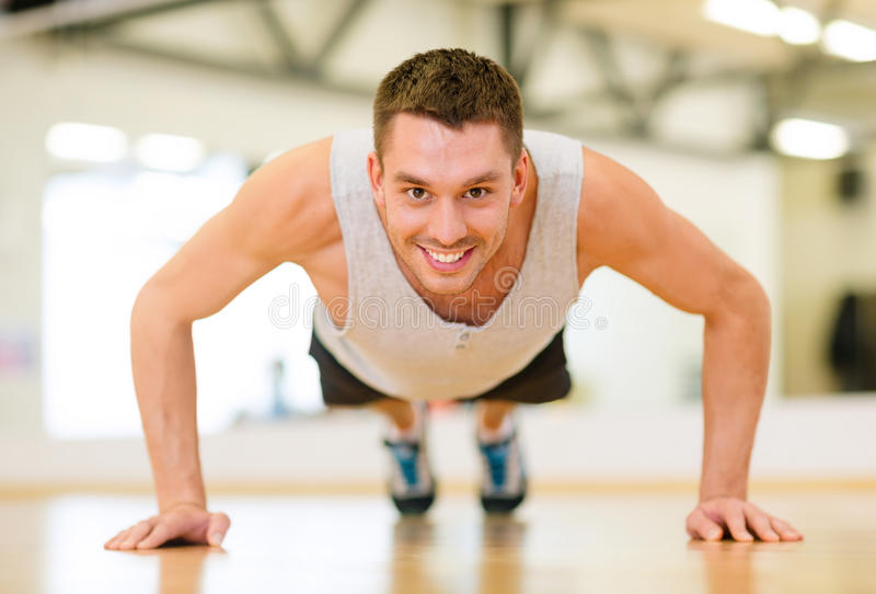 Smiling man doing push-ups in the gym. Fitness, sport, training, gym and lifestyle concept - smiling man doing push-ups in the gym royalty free stock photos