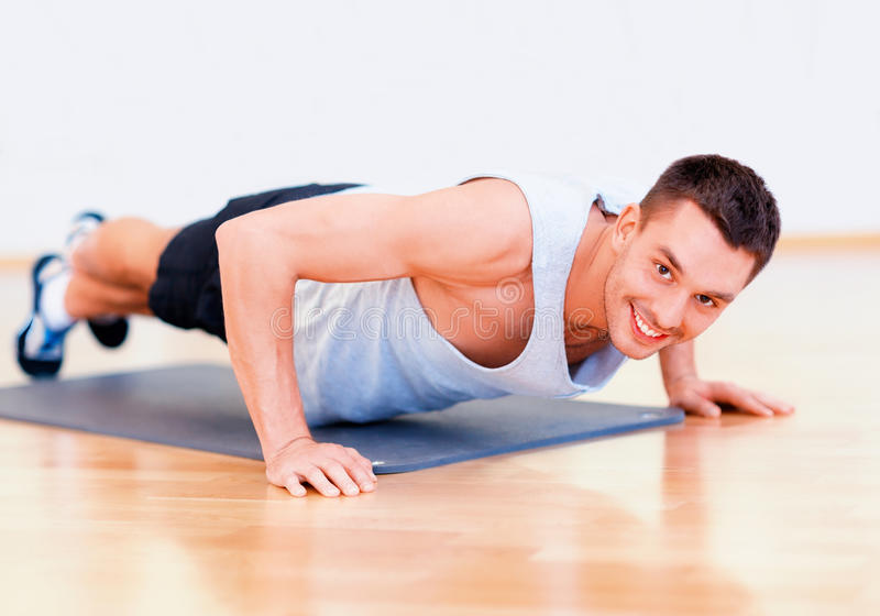 Smiling man doing push-ups in the gym. Fitness, sport, training, gym and lifestyle concept - smiling man doing push-ups in the gym or at home royalty free stock image
