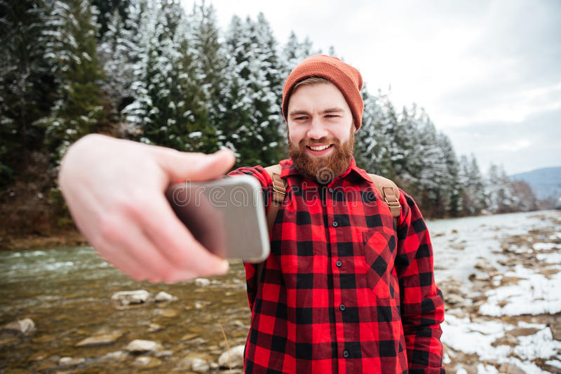 Smiling man doing selfie photo outdoors. With forest and river on background stock photos