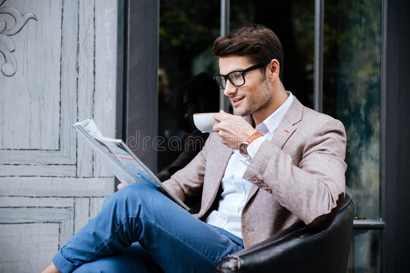 Smiling man drinking coffee and reading magazine in outdoor cafe royalty free stock photography