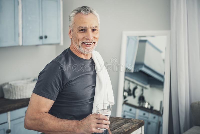 Smiling man drinking glass of water after morning shower royalty free stock images