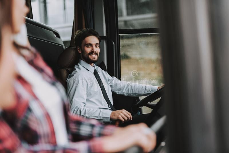 Smiling Man Driving Tour Bus. Professional Driver. Young Happy Man wearing White Shirt Sitting on Driver Seat and Looking at Woman. Attractive Confident Man at royalty free stock photography