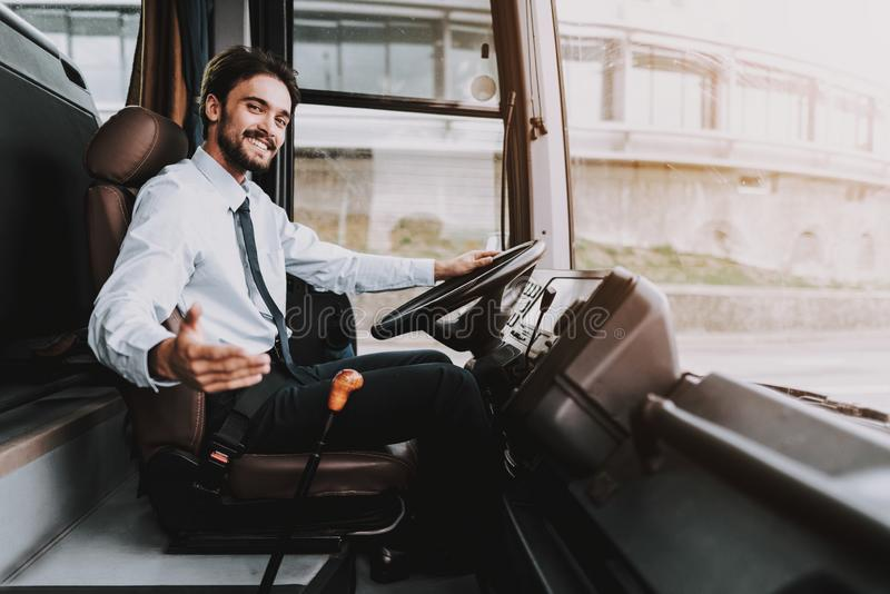 Smiling Man Driving Tour Bus. Professional Driver. Young Happy Man wearing White Shirt and Black Tie Sitting on Driver Seat. Attractive Confident Man at Work royalty free stock image