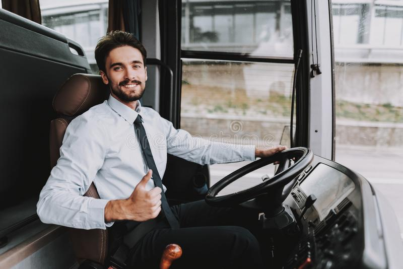 Smiling Man Driving Tour Bus. Professional Driver. Young Happy Man wearing White Shirt and Black Tie Sitting on Driver Seat. Attractive Confident Man at Work royalty free stock photo