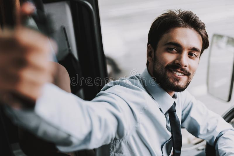 Smiling Man Driving Tour Bus. Professional Driver. Young Happy Man wearing White Shirt and Black Tie Sitting on Driver Seat. Attractive Confident Man at Work stock photography