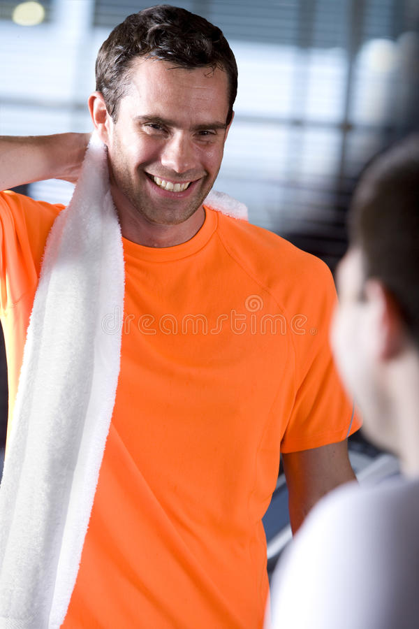 Smiling man drying sweat from neck and talking to woman in health club. Smiling men drying sweat from neck and talking to women in health club stock photography