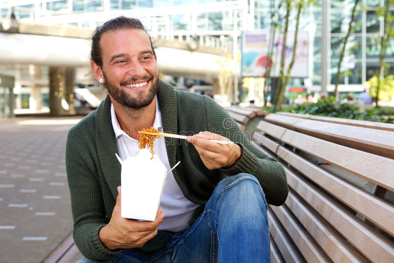 Smiling man eating chinese take away food stock photo