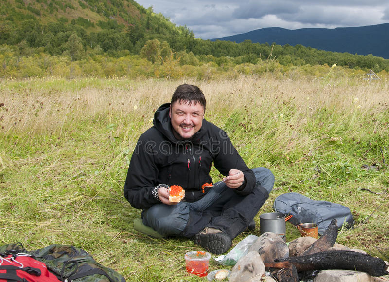 Smiling man eating red caviar in the open air stock photography