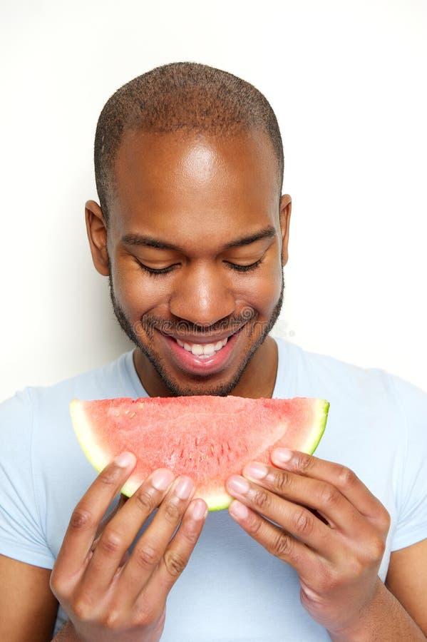 Smiling man eating watermelon. Close up portrait of a smiling man eating watermelon stock image