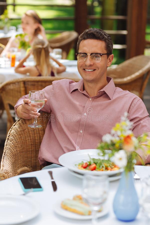 Smiling man feeling relaxed while having dinner stock photography