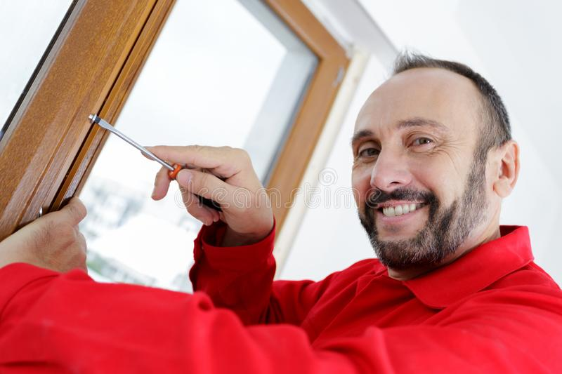 Smiling man fixing window using screwdriver royalty free stock photo