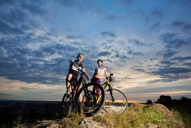 Smiling man and girl sitting on mountain bikes and smiling. royalty free stock photography