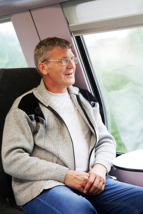 Smiling man goes in a train royalty free stock photo