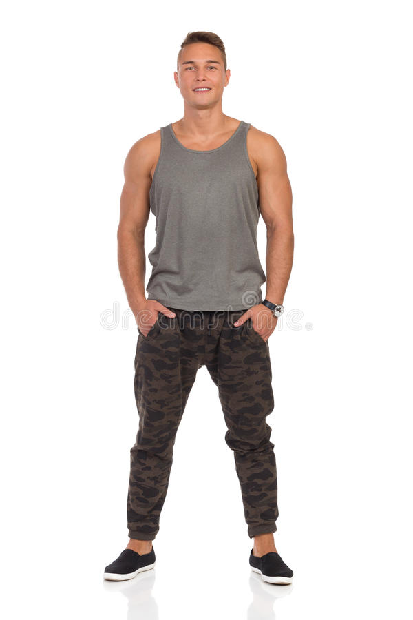 Smiling Man In Gray Tank Top And Camo Pants. Smiling young muscular man in pants with camo, gray tank top and black sneakers standing with hands in pocket. Front royalty free stock photography