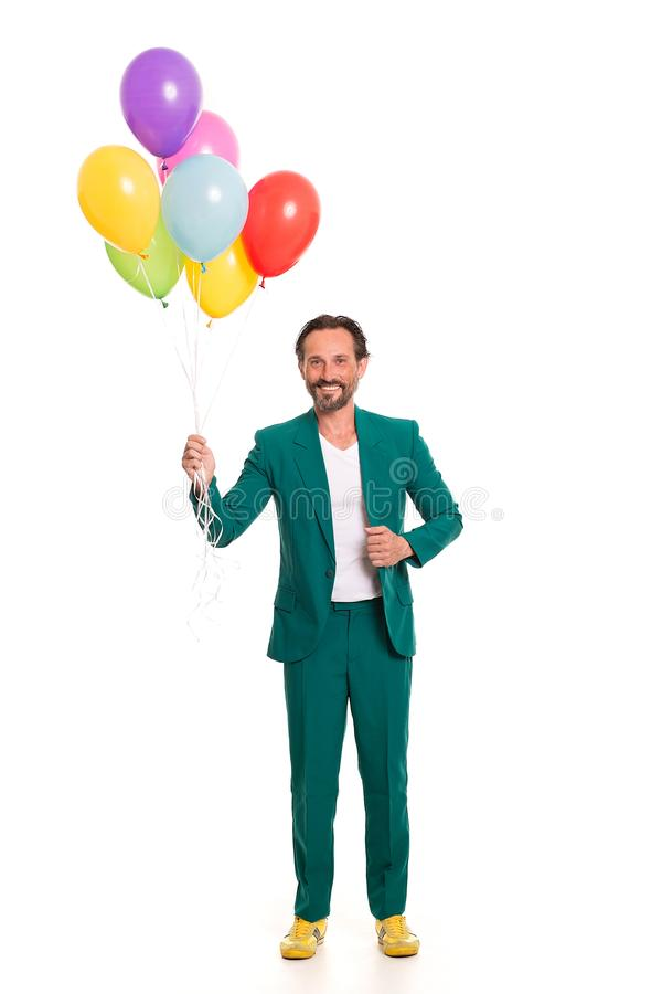 Handsome man in green suit. Smiling man in green suit. Holding colorful balloons stock images