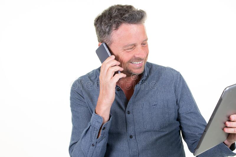 Smiling man happy handsome businessman using tablet computer while talking by phone. A Smiling man happy handsome businessman using tablet computer while talking stock images