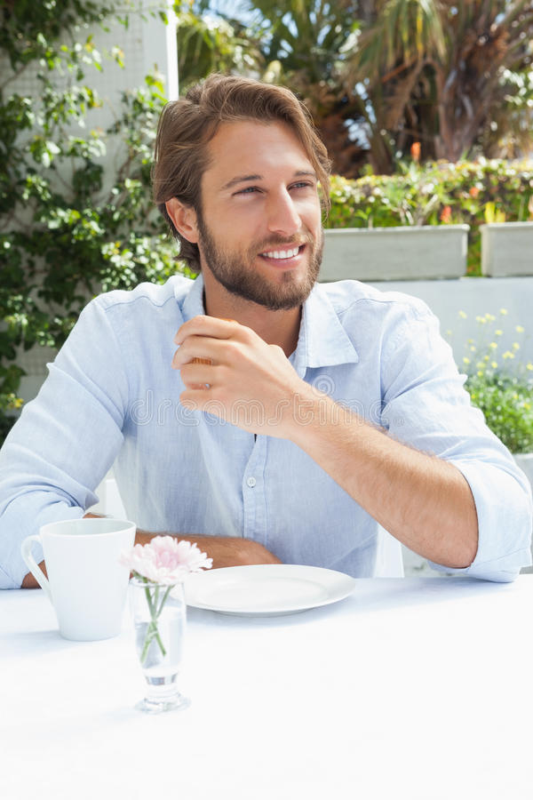 Smiling man having a coffee. Outside at the coffee shop stock photos
