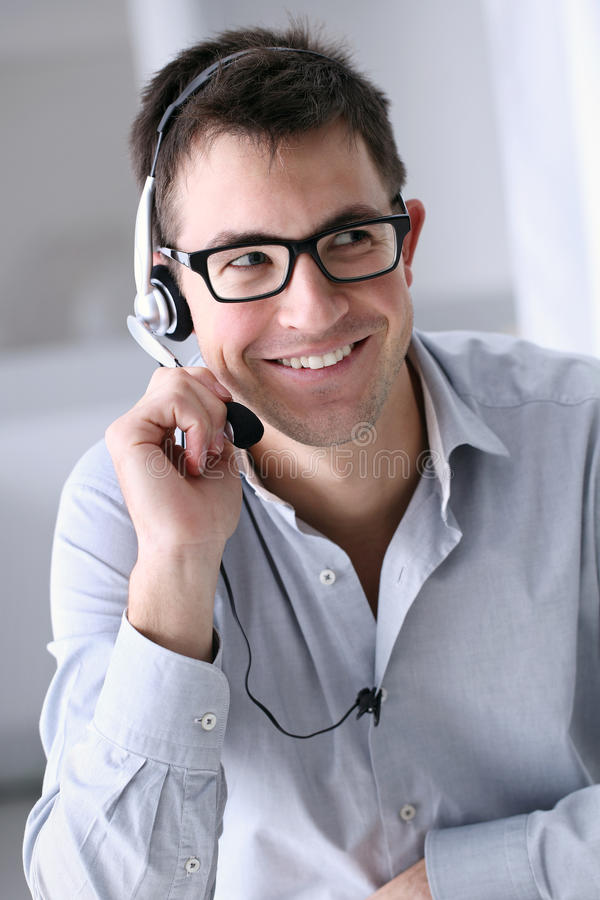 Smiling man with headphones in office, call center stock image