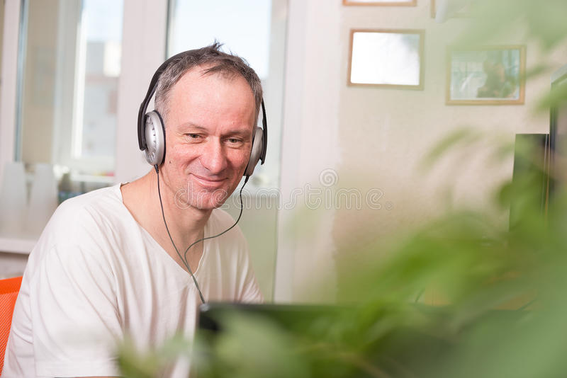 Smiling man in headphones sits near the computer. And looks at the screen, on the light blurred background - office at home, freelance work is your freedom stock photo