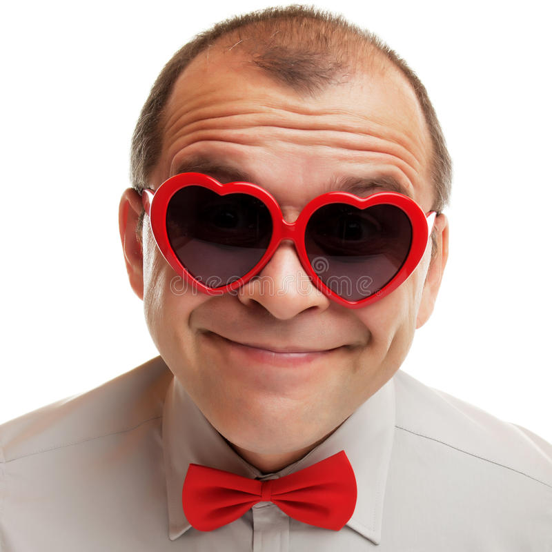 Smiling man with heart shaped sunglasses. Isolated on white royalty free stock photos