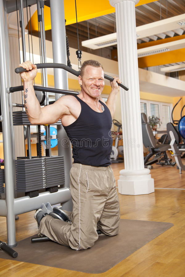 Download Smiling Man In His Forties Exercising In Gym Royalty Free Stock Photo - Image: 25171515