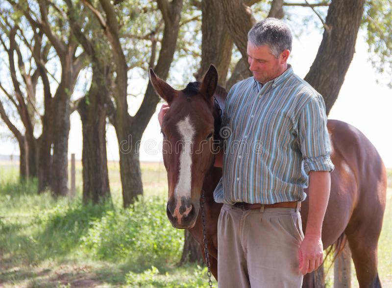 Smiling man with his horse in the Argentine countryside royalty free stock photo