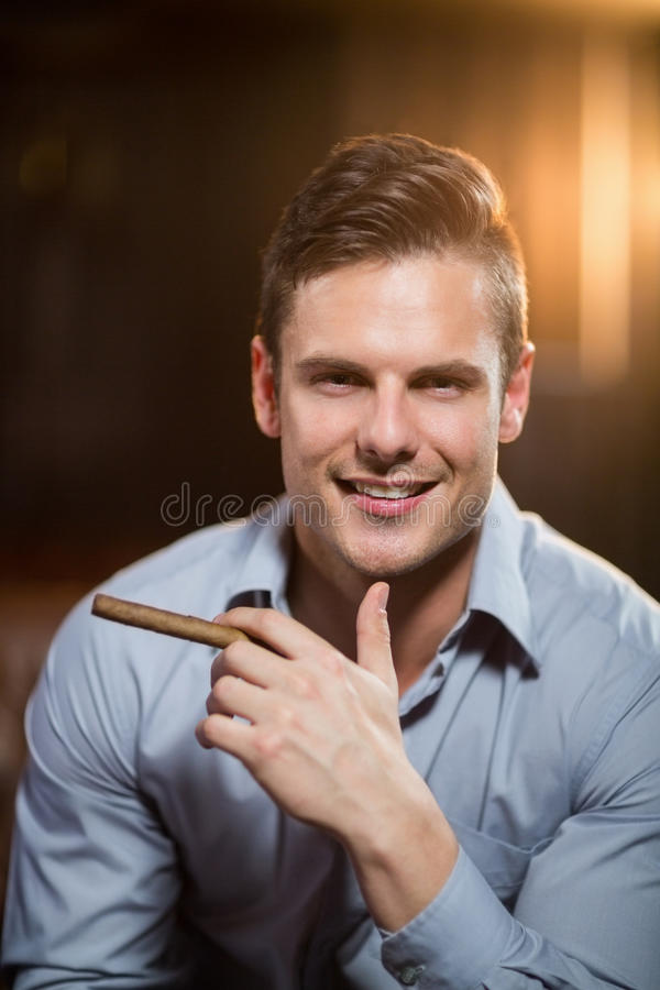 Smiling man holding a cigar in bar royalty free stock photo