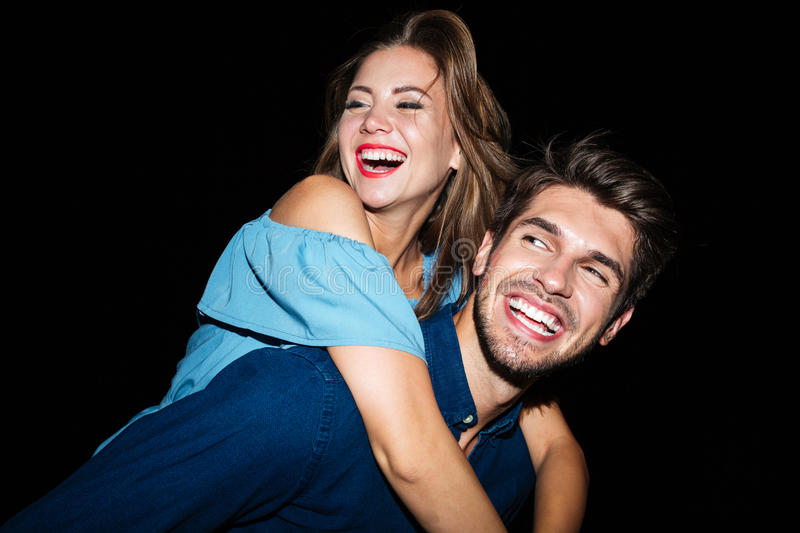 Smiling man holding girlfriend on his back at night stock image