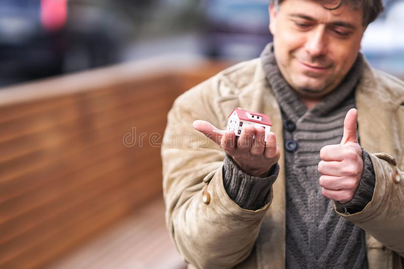 Buying a new house. Smiling man holding a model house and making the gesture of thumbs up royalty free stock photos