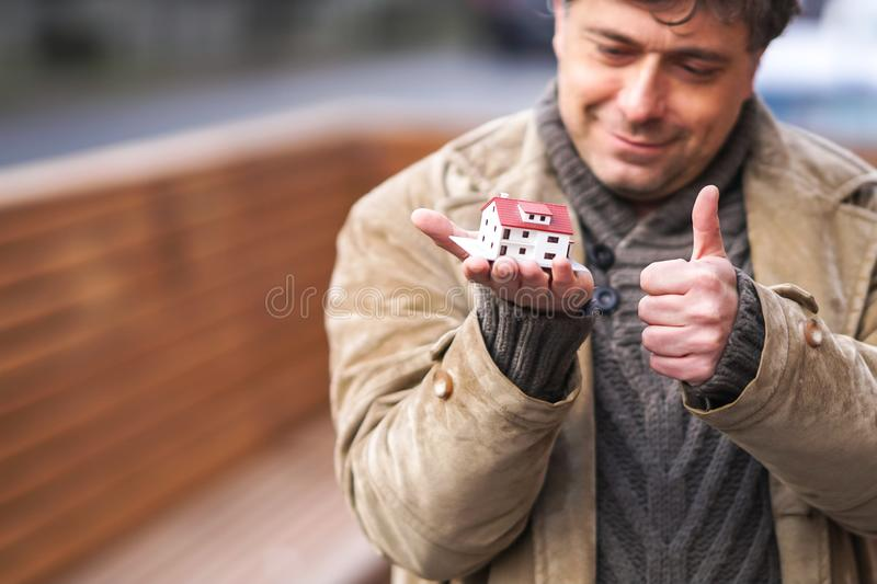 Buying a new house. Smiling man holding a model house and making the gesture of thumbs up stock photography