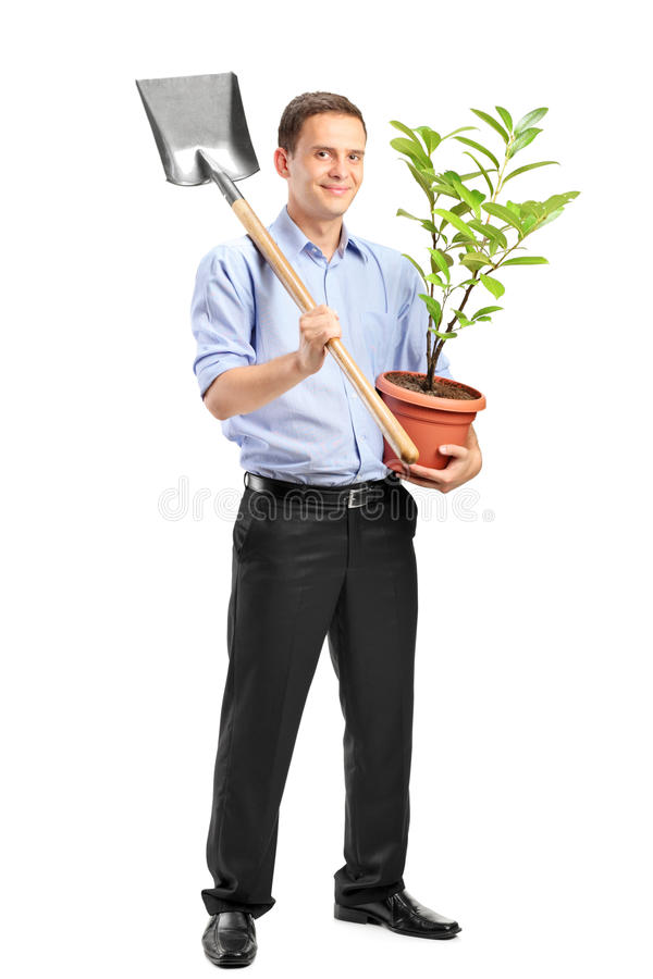 Smiling man holding a plant and a shovel stock images