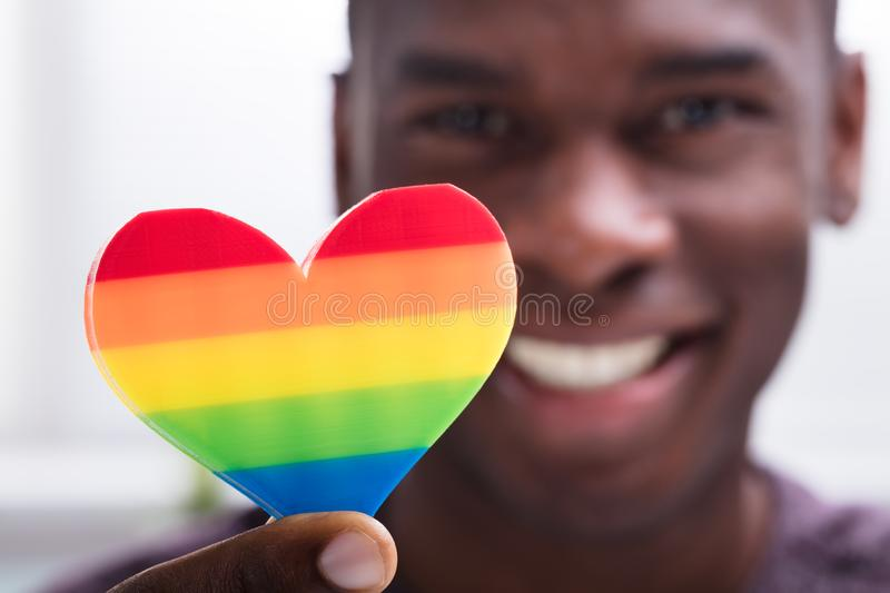Smiling Man Holding Rainbow Heart In His Hand. Against White Background royalty free stock photo