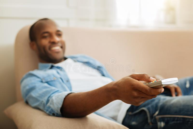 Smiling man holding remote control stock images