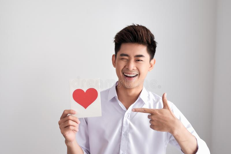 Smiling man holding valentine`s card standing on a white background royalty free stock photos