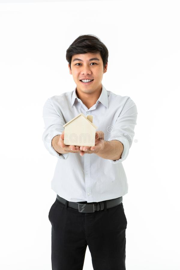 Smiling man holding wooden house model. Isolated on white background royalty free stock images