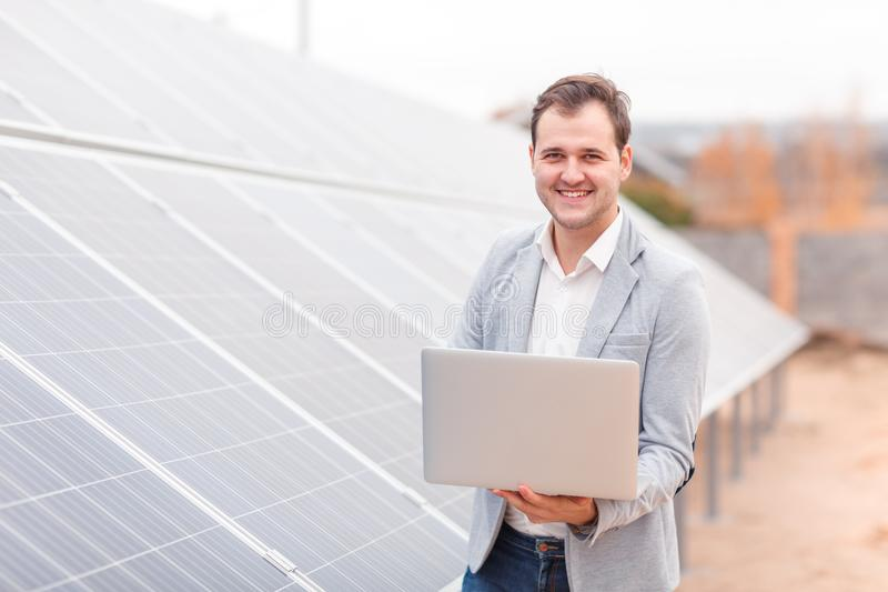 A smiling man, holds an laptop, standing next to the solar panel. Outdoors stock images