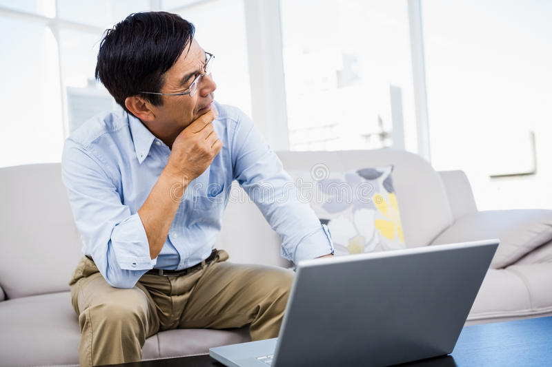 Smiling man at home on couch. Using laptop stock images