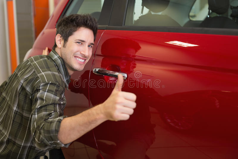 Smiling man hugging a red car while giving thumbs up. At new car showroom royalty free stock photography