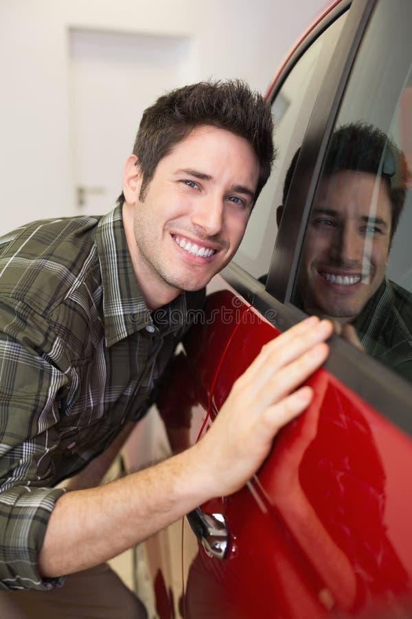 Smiling man hugging a red car. At new car showroom royalty free stock photo
