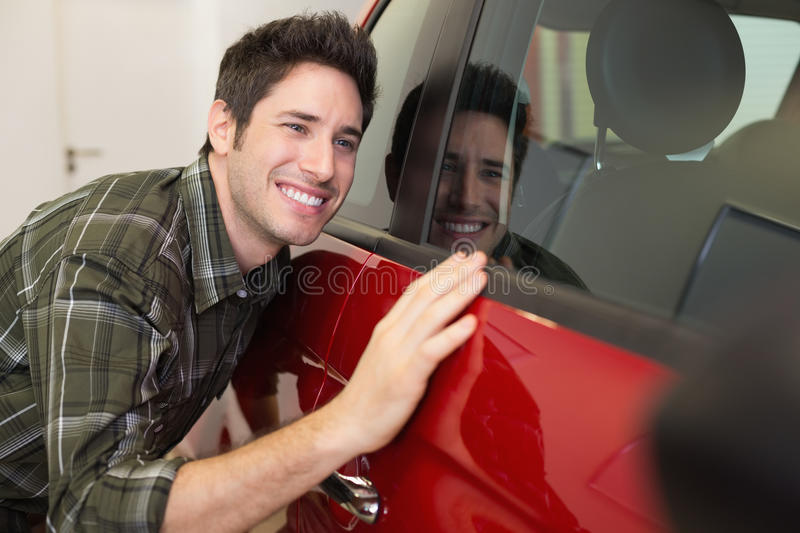 Smiling man hugging a red car. At new car showroom royalty free stock images