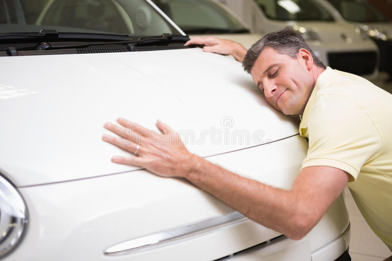 Smiling man hugging a white car. At new car showroom royalty free stock images