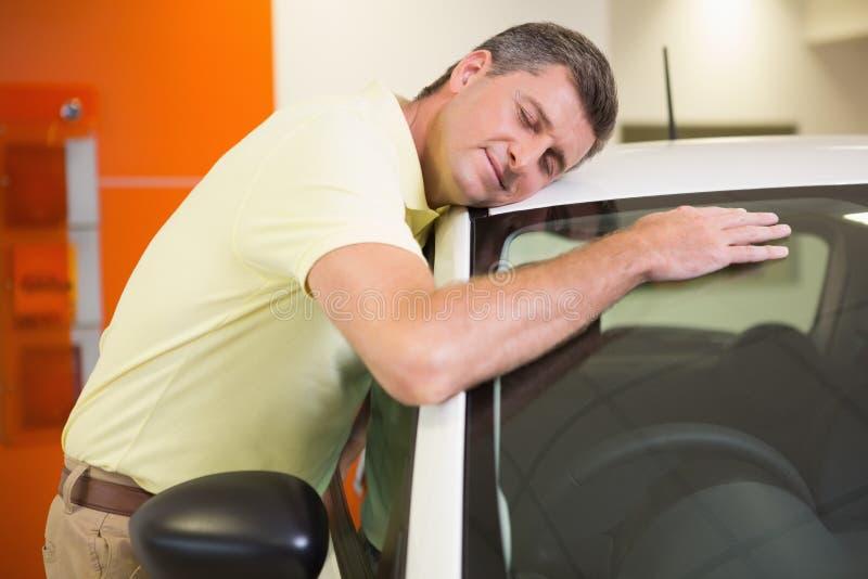 Smiling man hugging a white car. At new car showroom stock photos