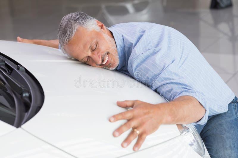 Smiling man hugging a white car. At new car showroom royalty free stock photos